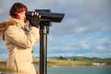 woman looking through sightseeing binoculars