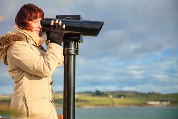 woman looking through sightseeing binoculars