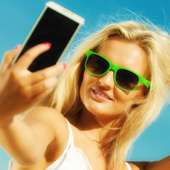Happy girl taking self picture with smartphone