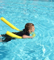 A young boy playing and having fun in a swimming pool