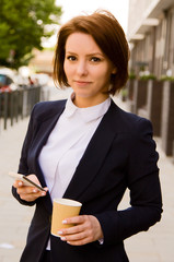 young business woman holding a coffee and a phone.