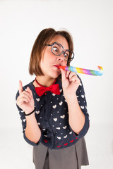 Cute nerdy girl blowing  a party horn.