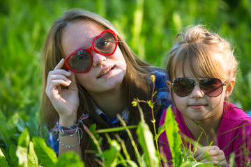 Two young sisters lying in the grass, sun-glasses.