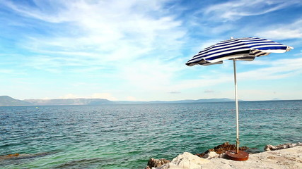 Alone beach retro style umbrella on the croatian shore