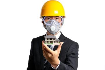 住宅の模型を持っているヘルメットをかぶったスーツのビジネスマン