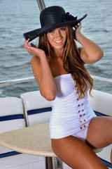 Glamor young woman posing on the luxury yacht wearing swimsuit.