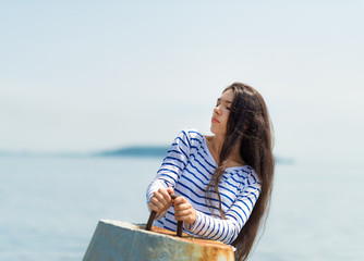 Girl in a striped T-shirt keeps for the breakwater.