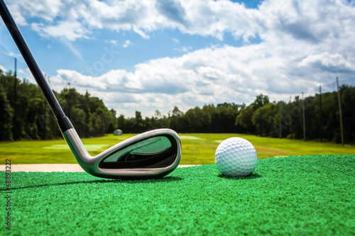 Close-up of a golf ball and a golf iron on a driving range - 68893222