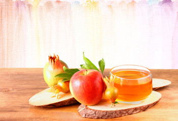 rosh hashanah concept - apple honey and pomegranate over wooden