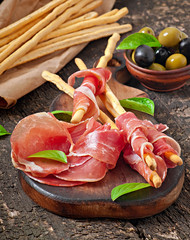 Grissini bread sticks with ham, olives, basil on table