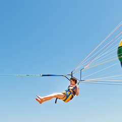 girl parasailing on parachute in blue sky