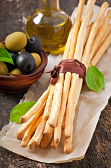 Grissini bread sticks on old wooden background