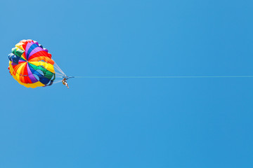 woman parakiting on parachute in blue sky