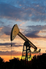 oil extraction by pumpjack at summer sunset