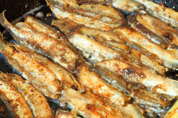fried fish capelin on black frying pan