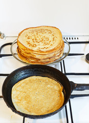 pancake in pan and stack of prepared pancakes