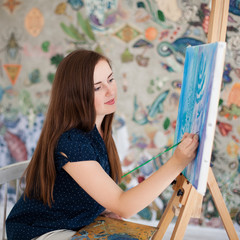 Artist painting picture on canvas whith watercolours