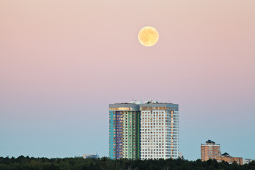 full moon in pink sky over urban houses