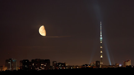 half moon over TV tower and city in summer night