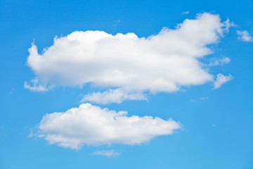 two puffy white clouds in blue sky