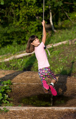 Girl hanging on rope
