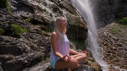 Young girl sitting and meditating under a tranquil waterfall