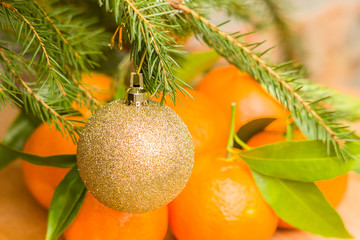 Christmas ball on fir branch on a background of tangerines