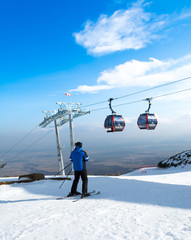 Male skier in the high Tatras with ski lift in the background