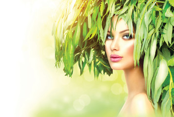 Girl with green leaves on her head. Beauty summer woman portrait
