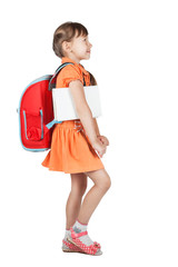 Cute schoolgirl goes with red backpack on her shoulders