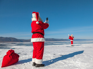 Santa Claus shoot on a smartphone of other Santa, walking on the