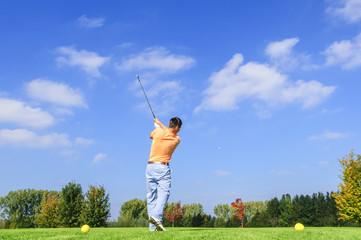 junger Golfspieler beim Abschlag