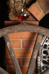 Glass of brandy on wooden wheel