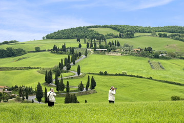 Two men taking pictures of the Tuscan landscape