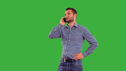very emotional man swears by phone on a green background.
