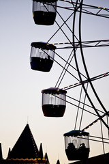 Silhouette of people riding on a ferris wheel