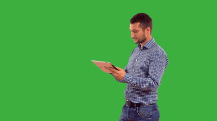 Young adult man talking on the tablet  on green background