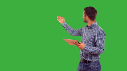 Young adult man showing copy space on green background