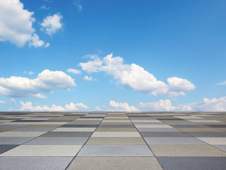 pavement with grey tiles and blue sky with clouds