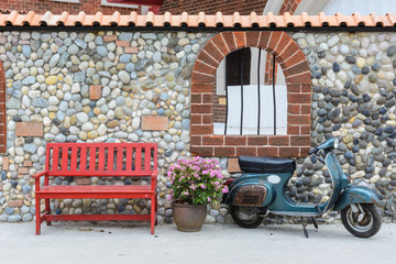 Red bench with flowers and motorcycle