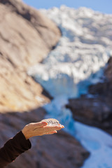 Hand with ice and Briksdal glacier - Norway