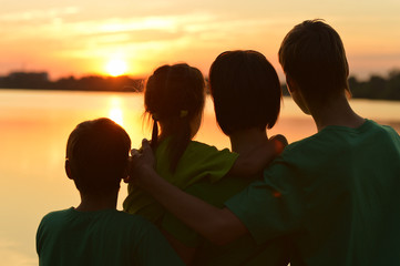 Family near the river against the sunset