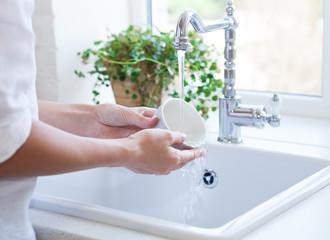 Woman washing dish in sink
