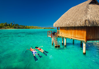 Young couple snorkling from hut over tropical lagoon