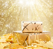 Gift box in gold wrapping paper with autumn leaves on the abstra