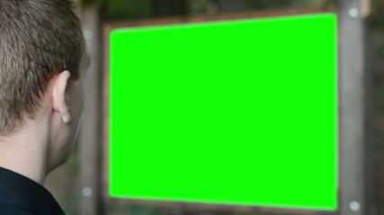 Young man looks at the information board- green screen