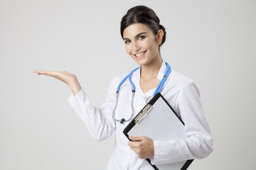 Smiling medical doctor woman with stethoscope. Present something