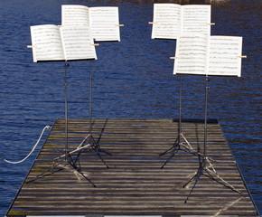 Vier Notenständer auf einem Steg am See
