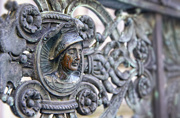 Vintage bronze fence with human head at Piazza Duomo in Bergamo