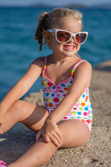little girl at the beach with big sunglasses